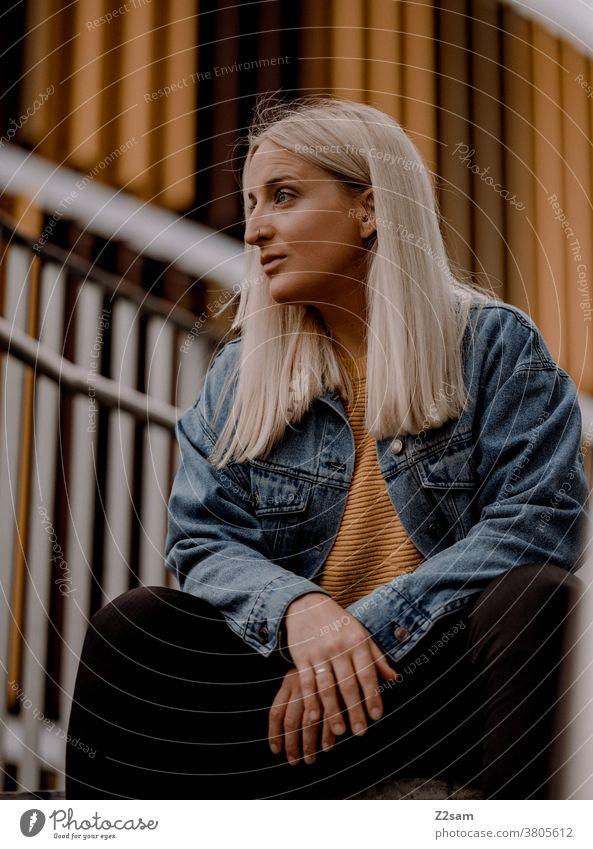 Junge blonde Frau sitzt auf der Treppe im urbanen Raum jeansjacke lange haare lifestyle portrait hübsch schön woman erholung selbstbewusst stadt innenstadt