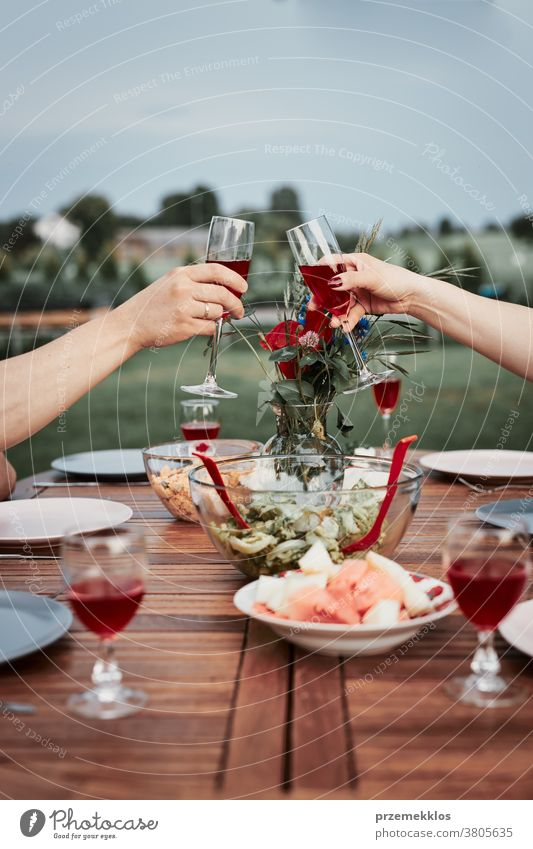 Couple making toast during summer outdoor dinner in a home garden feast having picnic food man together woman barbecue table eating gathering people lifestyle