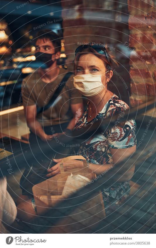 Family sitting in coffee shop at store front in the city center, wearing the face mask to avoid virus infection caucasian conversation covid-19 lifestyle