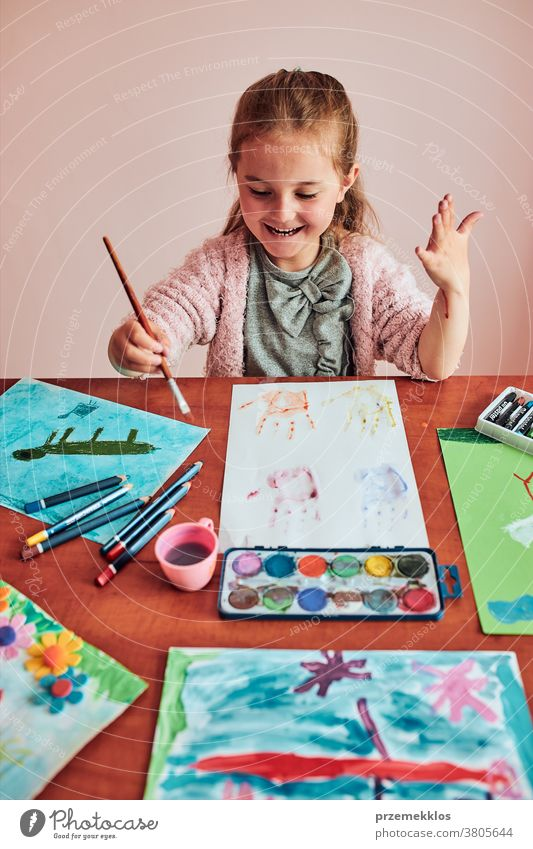 Little girl preschooler painting a picture using colorful paints and crayons child dye education art home paper childhood creation craft table creativity kid