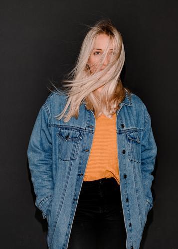 Fashion-Portraits einer jungen Frau blonde flashlook jeansjacke paparazzi-look trashig mode pullover lange haare hübsch wind wehen portrait beautiful lifestyle