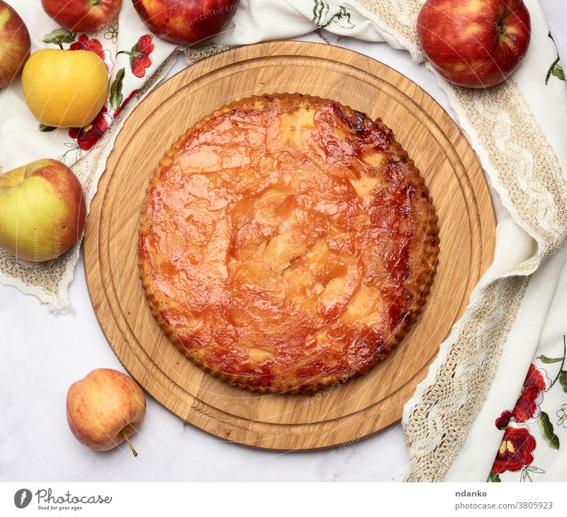 baked round apple pie on wooden board and fresh apples above cake pastry dessert homemade food american delicious thanksgiving traditional fruit sweet autumn
