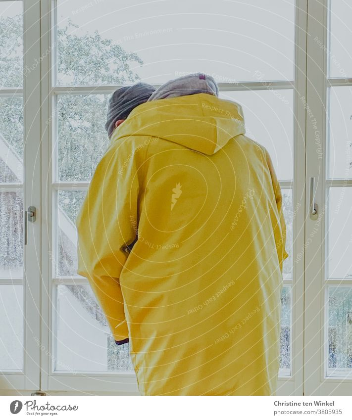Man stands at the window in rainy weather and puts on a Frisian mink | trapped in plastic friesennerz Rain jacket Raincoat Rainy weather Bad weather