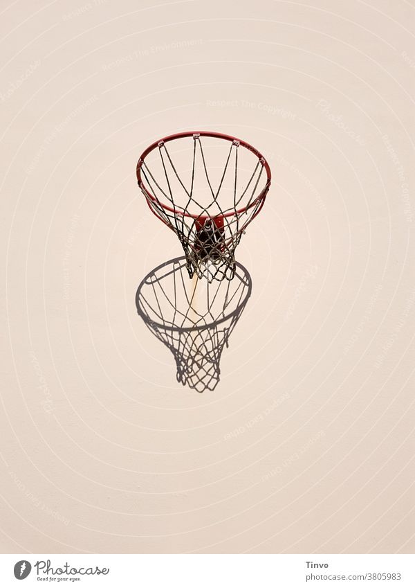 Basketball hoop and its shadow on a light-coloured house wall Basketball basket Shadow Sports Athletic Leisure and hobbies Copy Space top Copy Space bottom
