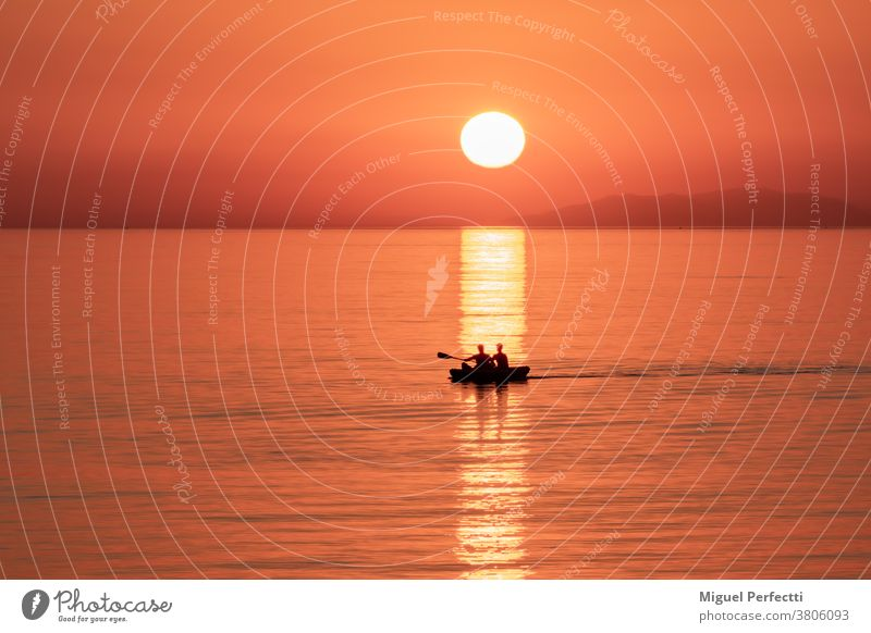 Silhouette of two people in a canoe passing by the reflection of the sun in the sea at sunset. beach silhouette orange kayak horizon browsing boat red landscape