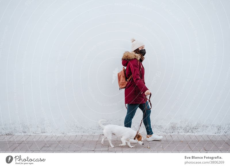 woman wearing protective mask walking by the city with her adorable jack russell dog. Lifestyle outdoors adult allergic autumn background care caucasian