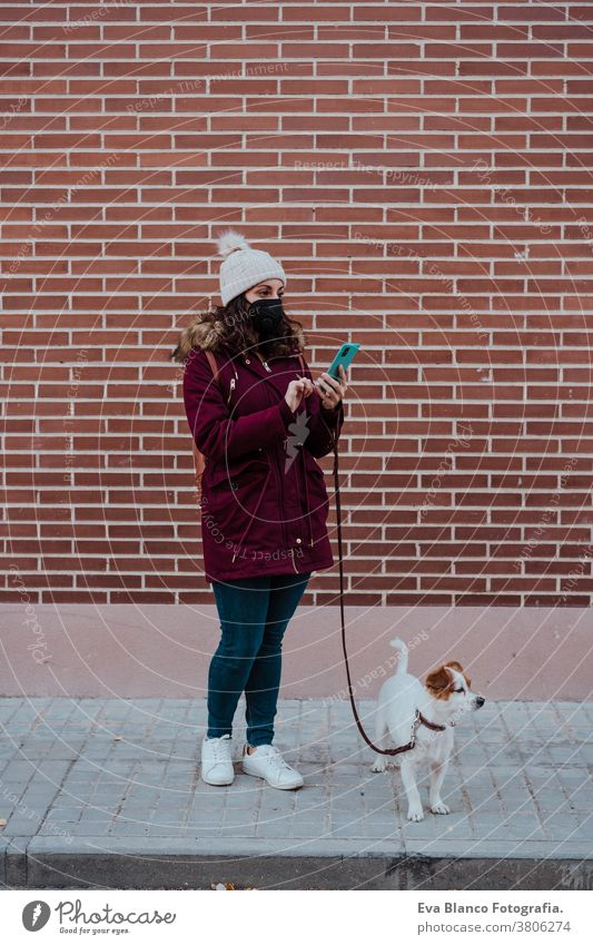 woman wearing protective mask, using mobile phone, walking at the city with her adorable jack russell dog. Lifestyle outdoors allergic autumn brick wall care