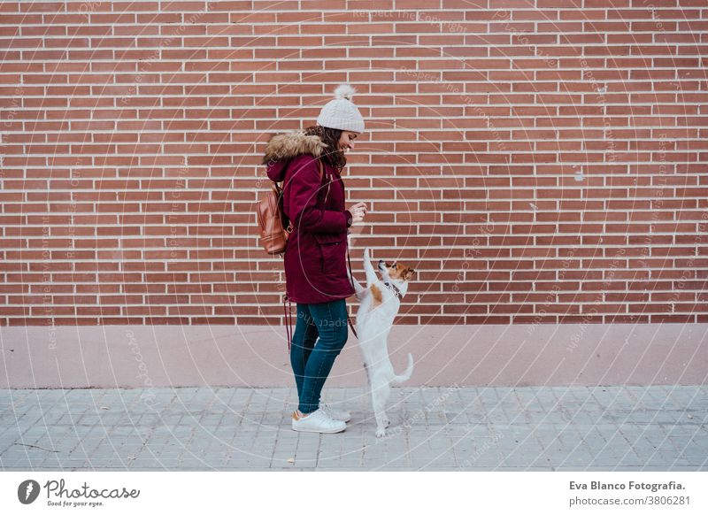 woman at the city with her adorable jack russell dog. Lifestyle outdoors autumn brick wall bulldog casual clothing caucasian cheerful coat cold collar cute