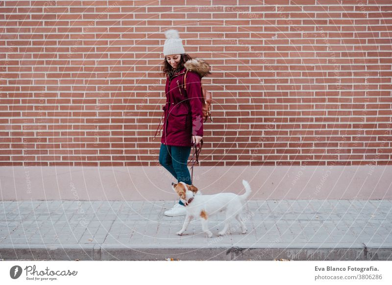woman at the city walking with her adorable jack russell dog. Lifestyle outdoors autumn brick wall bulldog casual clothing caucasian cheerful coat cold collar