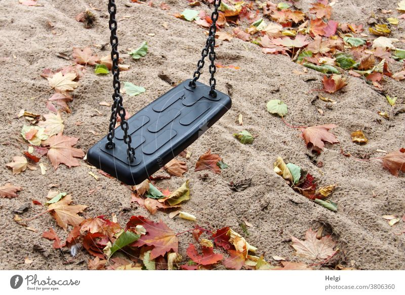 Autumn atmosphere on the playground - swing hangs over rain-soaked sandy ground covered with autumn leaves Swing Playground Shadow Maple leaf Autumnal colours