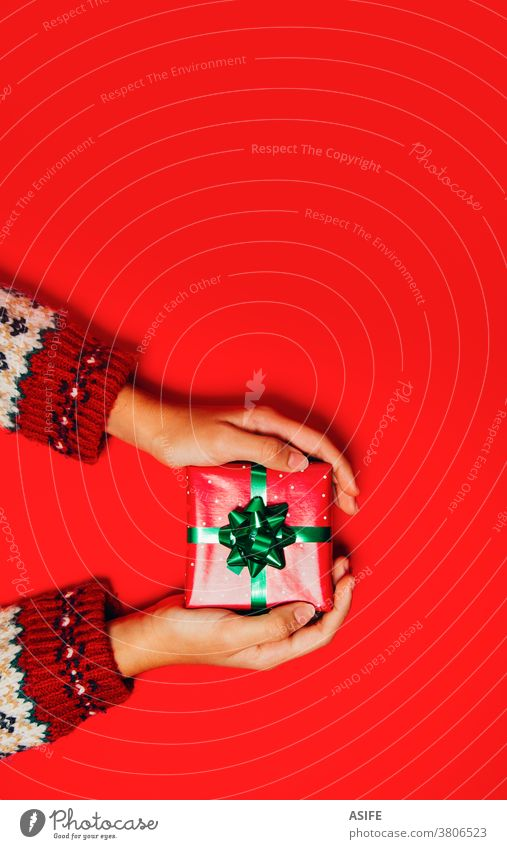 Female hands with a winter sweater holding a Christmas gift on a red background. box present giving receiving package top view surprise high angle view give