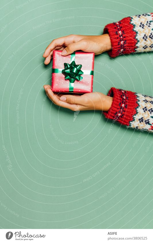 Female hands with a winter sweater holding a Christmas gift on a green background. box present giving receiving package top view surprise high angle view give