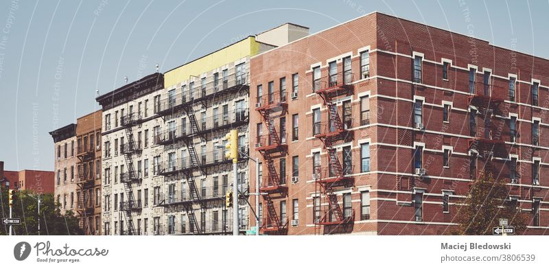 Buildings with fire escapes in Harlem New York, USA. city building old house retro home urban residential NYC manhattan panorama outdoors architecture filtered