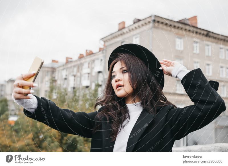 Young asian female in dark coat and hat taking a selfie outdoors mobile photo woman lady camera smartphone girl lifestyle young fun picture beautiful portrait