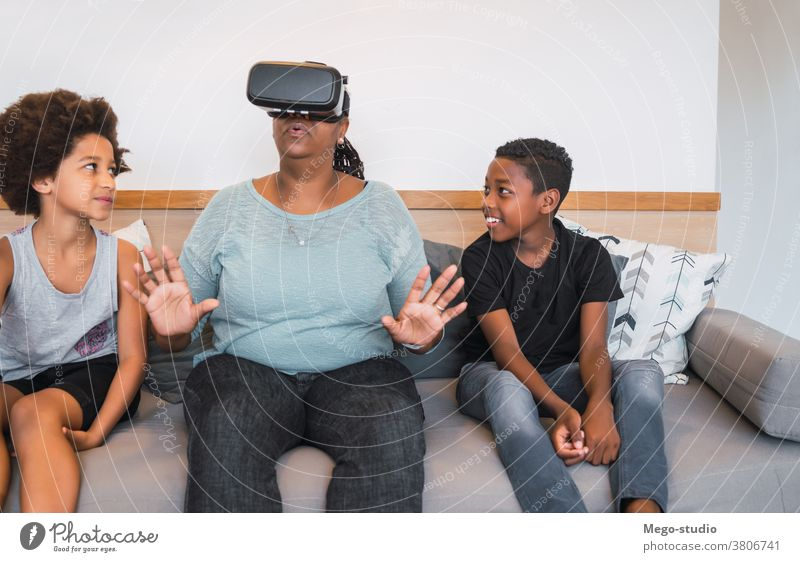 Grandmother and grandchildren playing together with VR glasses. grandparent reality virtual simulation modern device concept simulator virtual reality