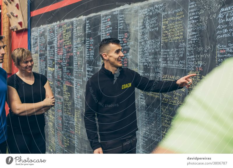 Coach explaining to athletes in the gym coach results laughing fun enjoying workout blackboard instructor cross fit cross-training cheerful fitness man exercise