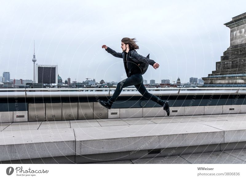 The dynamic young man jumps or hovers over Berlin with big steps panorama Reichstag Bundestag dome Roof Above Tall Man younger Dynamic Elated Spirited Jump far