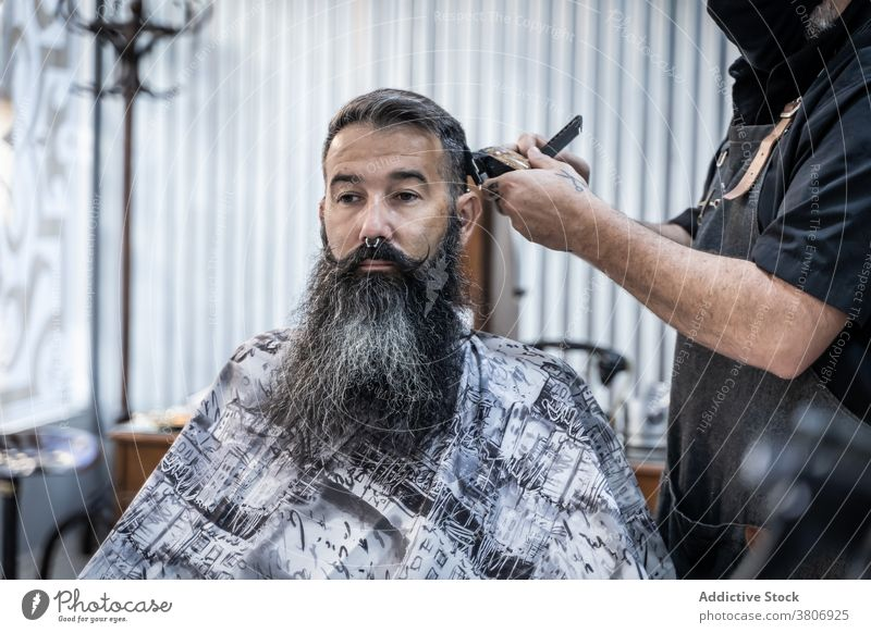 Bearded client getting haircut in barber shop barbershop trimmer beard grooming salon beauty style hipster masculine male middle age mature fashion work comb