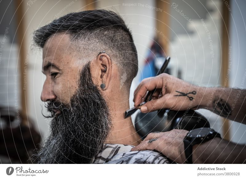 Barber making haircut to bearded client barbershop razor shave grooming salon beauty style hipster masculine male middle age mature fashion work occupation
