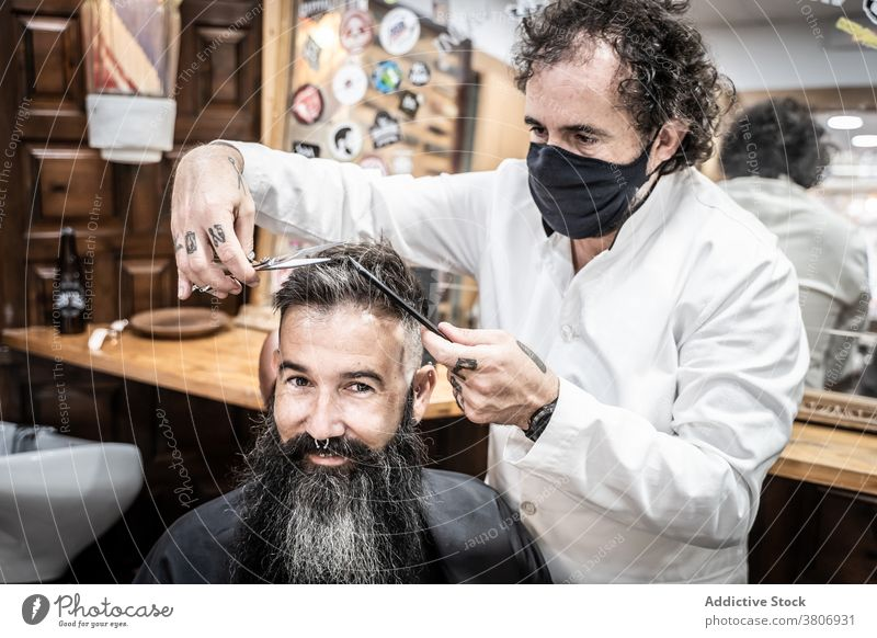 Happy hipster man getting haircut in barbershop beard grooming client salon scissors style beauty comb masculine male middle age mature fashion mask coronavirus
