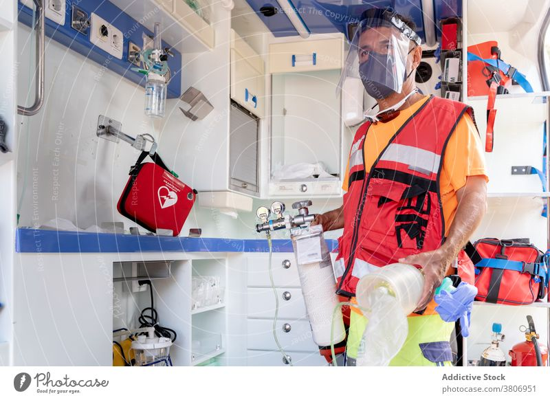 Anonymous lifeguard in visor with medical equipment in ambulance protective shield uniform profession work car worker first aid kit professional mask roll man