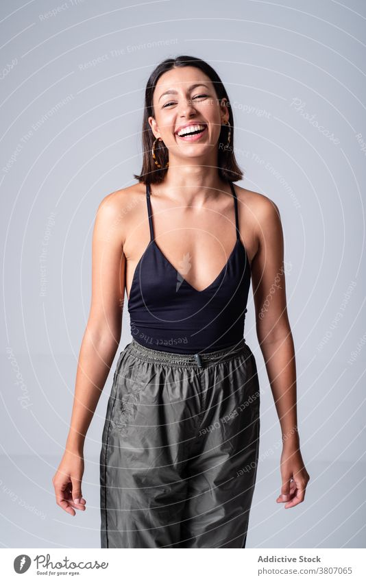 Joyful young woman in tight black top in studio expressive grace appearance style outfit cool gorgeous charming toothy smile delight excited figure attractive