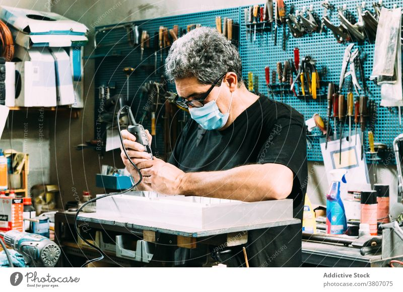 Professional workman in mask soldering details in workshop craftsman focus workplace profession small business handyman instrument concentrate professional