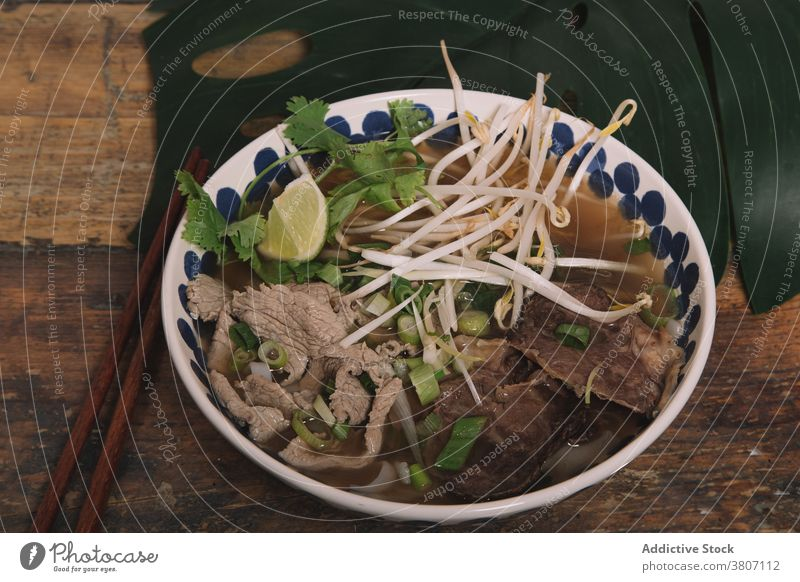 Bowl of tasty Vietnamese soup with beef on table pho vietnamese food bean sprout bowl tradition serve fresh parsley green onion lime piece meal dish vegetable
