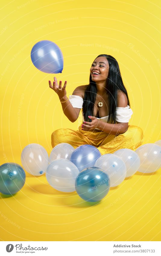 Cheerful young African American female playing with balloons in studio woman happy cheerful joy style model smile fashion playful positive optimist ethnic black