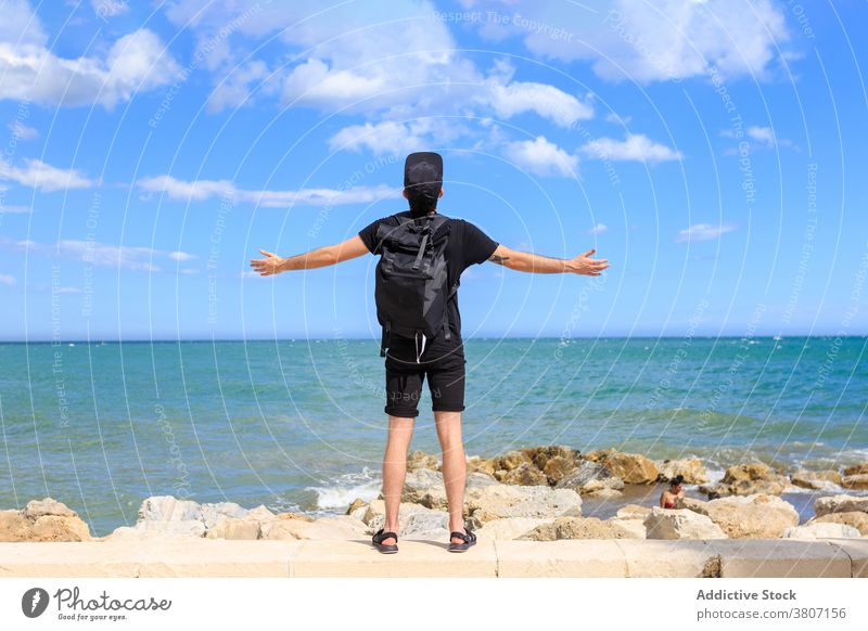 Male traveler enjoying seascape under sky during summer trip tourist backpack dreamy freedom man ocean nature blue sky cloudy apparel modern mindfulness