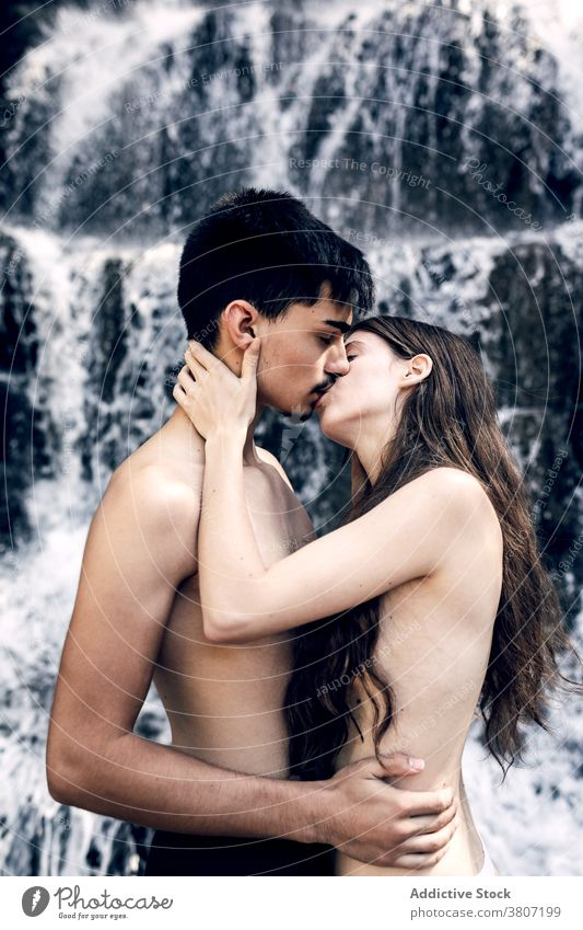 Tender naked couple embracing near waterfall tender hug nature love kiss kissing nude carefree embrace summer affection romantic together enjoy relationship