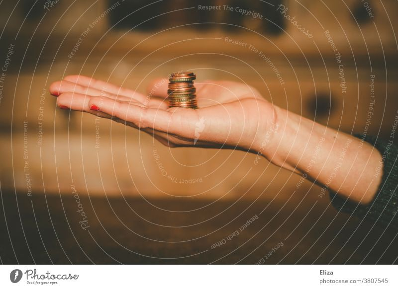 A woman holds a tower of change in her hand. Savings, money, finance. small change Coins Money Save Hand Tower Loose change Paying Little Woman investment