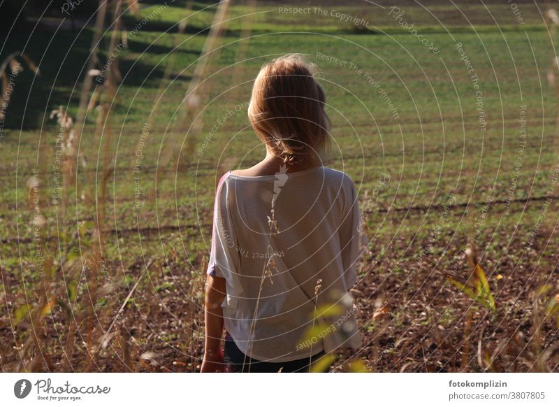 Girl looking at a fresh green field acre spring Growth Wait Arable land back view Back Field Landscape Agriculture Spring Spring fever Sprout wax Nature
