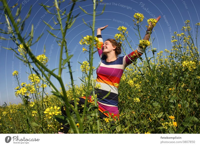 young woman jumping with arms up in a rape field Canola Canola field Field Optimism Young woman Woman Self-confidence Joie de vivre (Vitality) Happy pleased