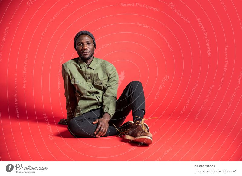 Young Black Man Posing Seated on Studio Floor man sit black content pose African ethnicity one person male one man only 20-30 years old handsome studio shot