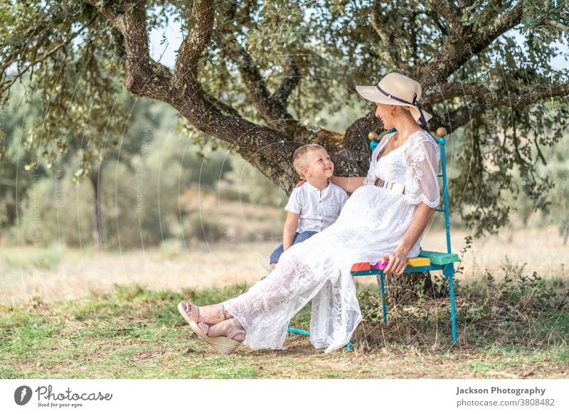 Pregnant woman spending time with her little son in the nature pregnant pregnancy mother family playing showing toddler boy baby expecting belly girl summer