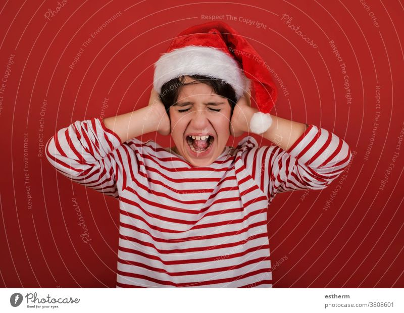 angry kid wearing Santa Claus hat with his hands on his head child christmas santa claus screaming desperate christmas eve furious stressed nervous despair