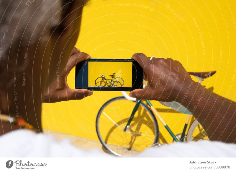 Black man taking a photo of his bike with the phone on a yellow mobile bycicle selling online sell a bycicle sell a bike selling a bike black man sell online