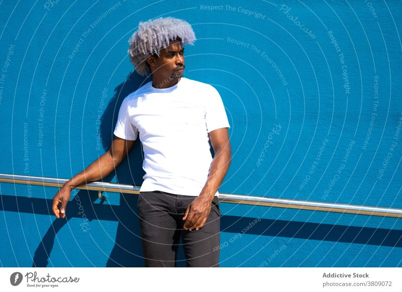 Black man with afro hair dressed in white leaning against a blue black man afro black man afro man leaning on a wall white shirt blue background blue wall