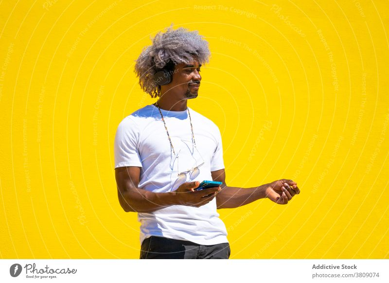 Black man with afro hair listening to music with headphones and black man listen to music earphones dancing dance dancing teacher yellow background casual
