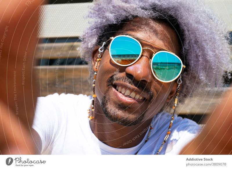 Black man with afro hair smiling and taking a selfie. Black man black man african american taking a picture portait style sunglasses smile happy happiness photo