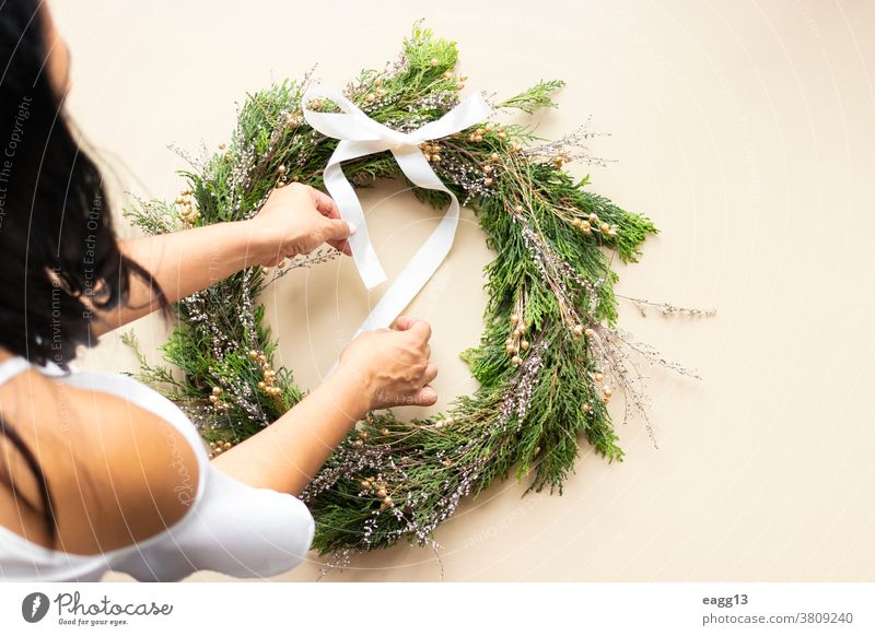 Cute woman decorates advent wreath with her hands Christmas arrangement christmastime circle concept create creative creativity december decorating decorations