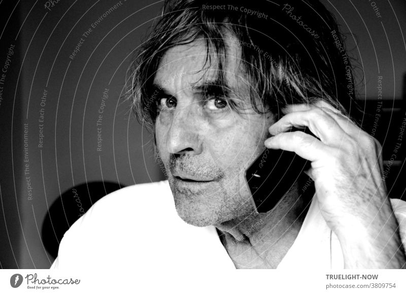 Don't disturb me when I'm talking on the phone, the somewhat wild looking, unshaven man with long hair in half profile and white T-shirt seems to think while holding a cordless phone to his ear