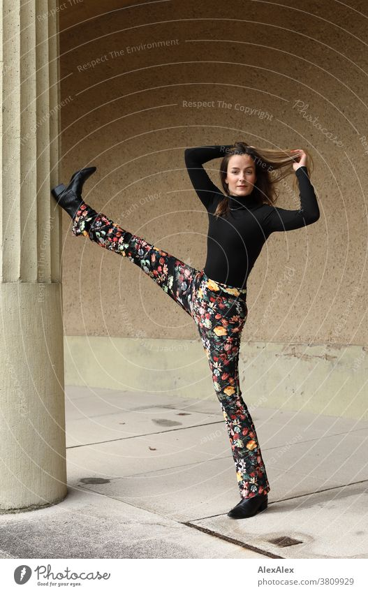 Portrait of a young dancer holding one leg up on a column Woman 18 - 30 years pretty fit Slim smart kind Pleasant Attractive Brunette Long-haired salubriously
