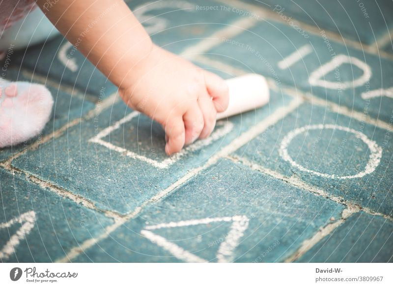 Toddler holds chalk in his hand and paints Chalk Painting (action, artwork) Hand Child Creativity Girl street-painting chalk Employment Infancy fun Draw