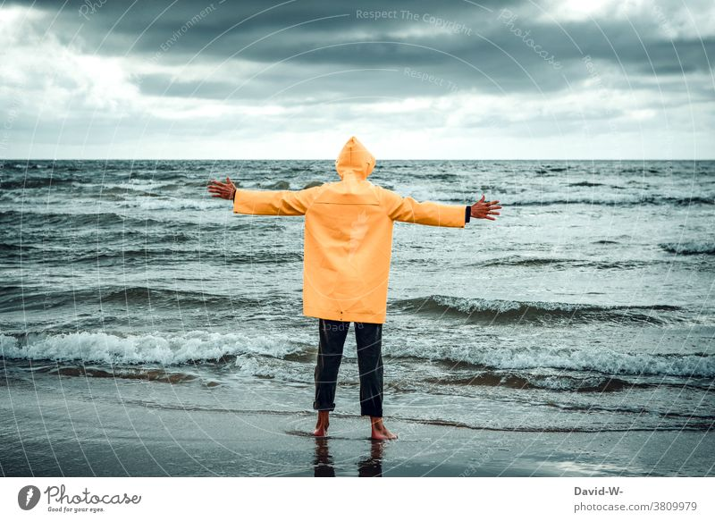 Man in Frisian mink stands with outstretched arms at the sea Ocean ocean Embrace friesennerz Storm Waves Vacation & Travel Water coast Clouds stormy Gigantic