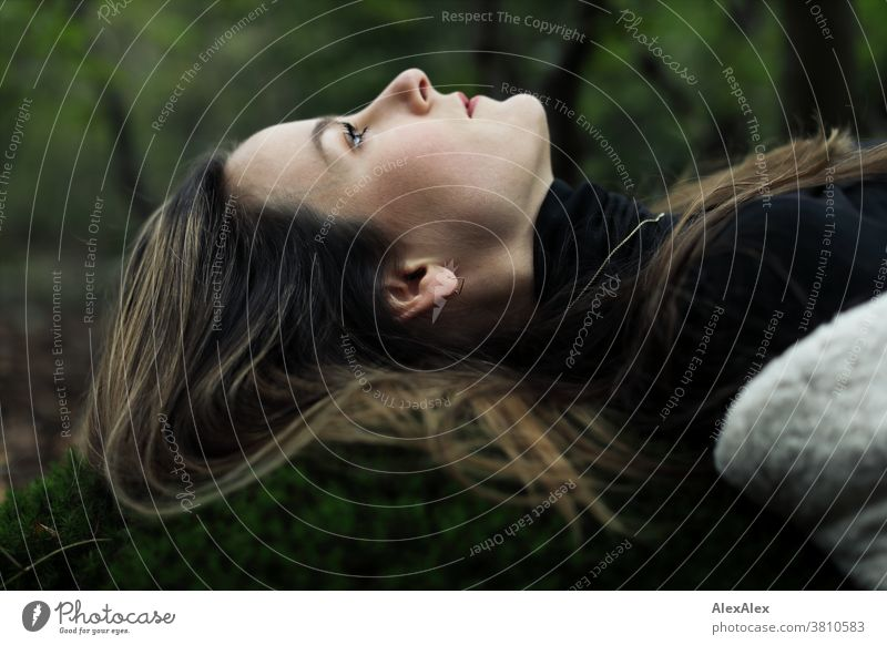 Lateral portrait of a young woman lying on a moss hill in the forest and looking up Woman 18 - 30 years pretty fit Slim smart Pleasant Attractive Brunette