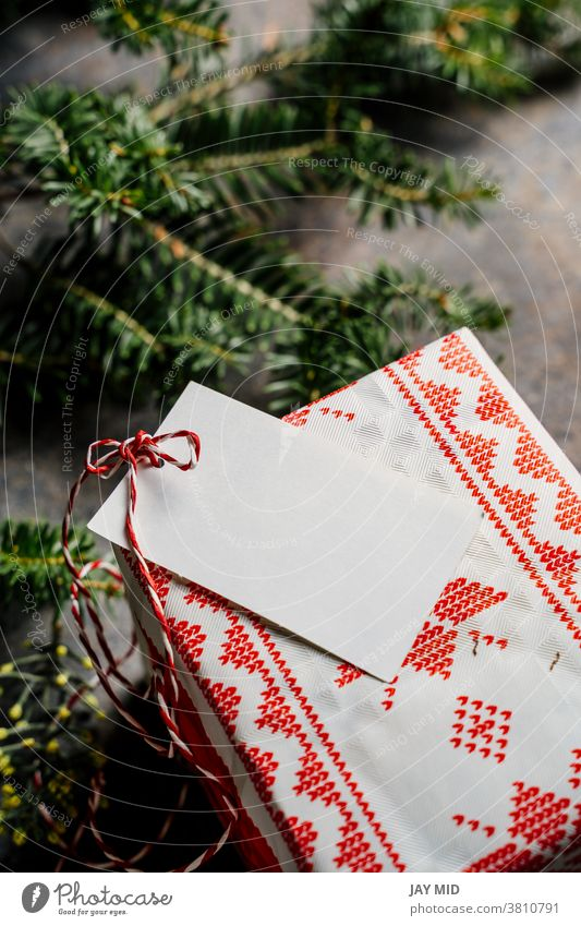 Wrapped christmas gift box, with empty tag and red tape, surrounded by pine branches on grunge blue background craft paper wrapped label rustic tradition loop