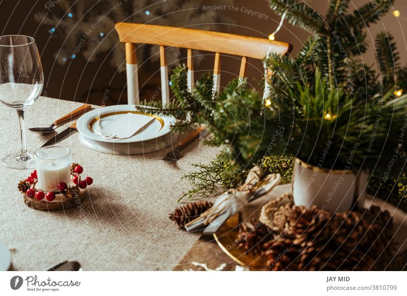 Cosily laid Christmas table, decorated with pine branches and rustic tablecloth in the living room with tree lighting Thanksgiving Table Set meal Menu Home Food