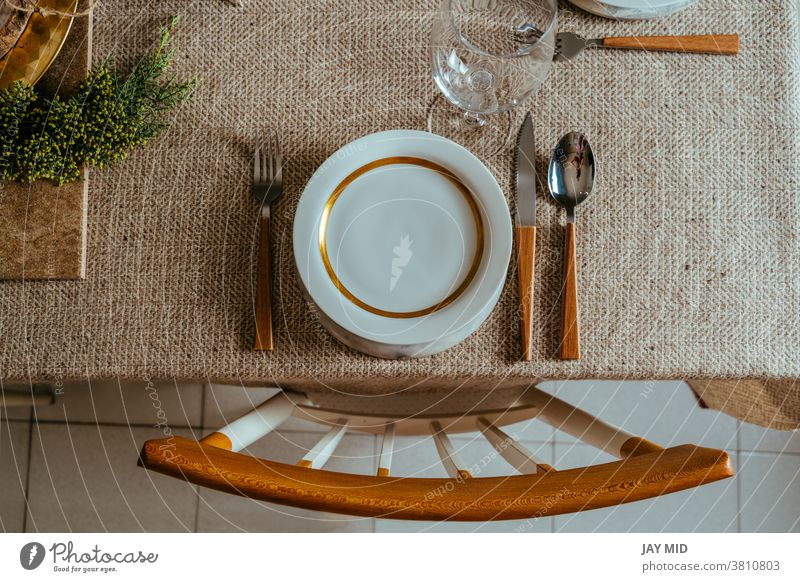 Holiday Gold place setting,  Christmas table with ornaments and natural pine branch on the livingroom home christmas thanksgiving menu food happy above